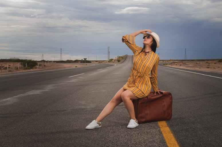 photo of woman sitting on luggage bag
